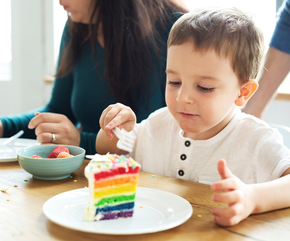 Little boy eating a rainbow colored cake