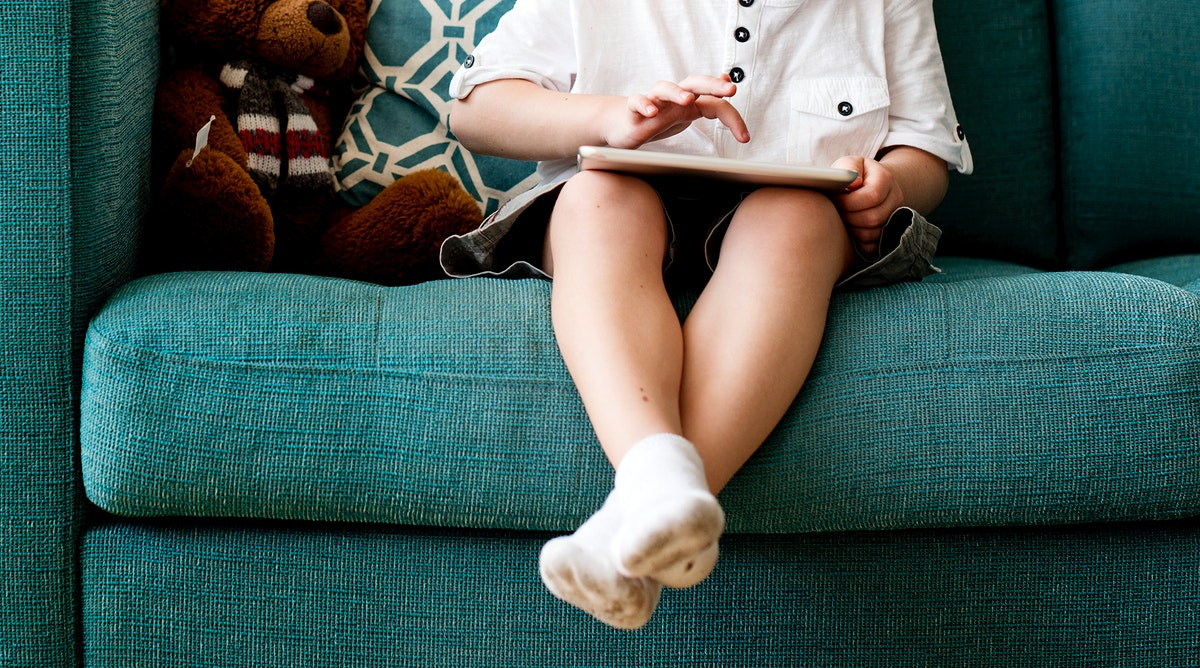 Little boy sat on a couch using digital tablet