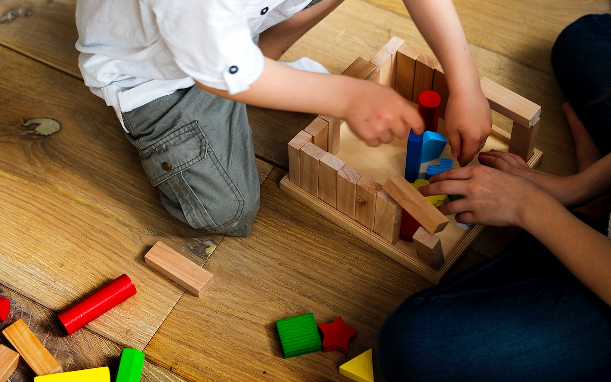 Little kids playing with toy blocks