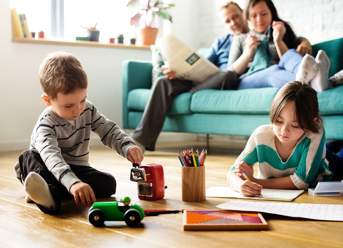 Children having fun playing, while their parents on the couch are having a quality time together