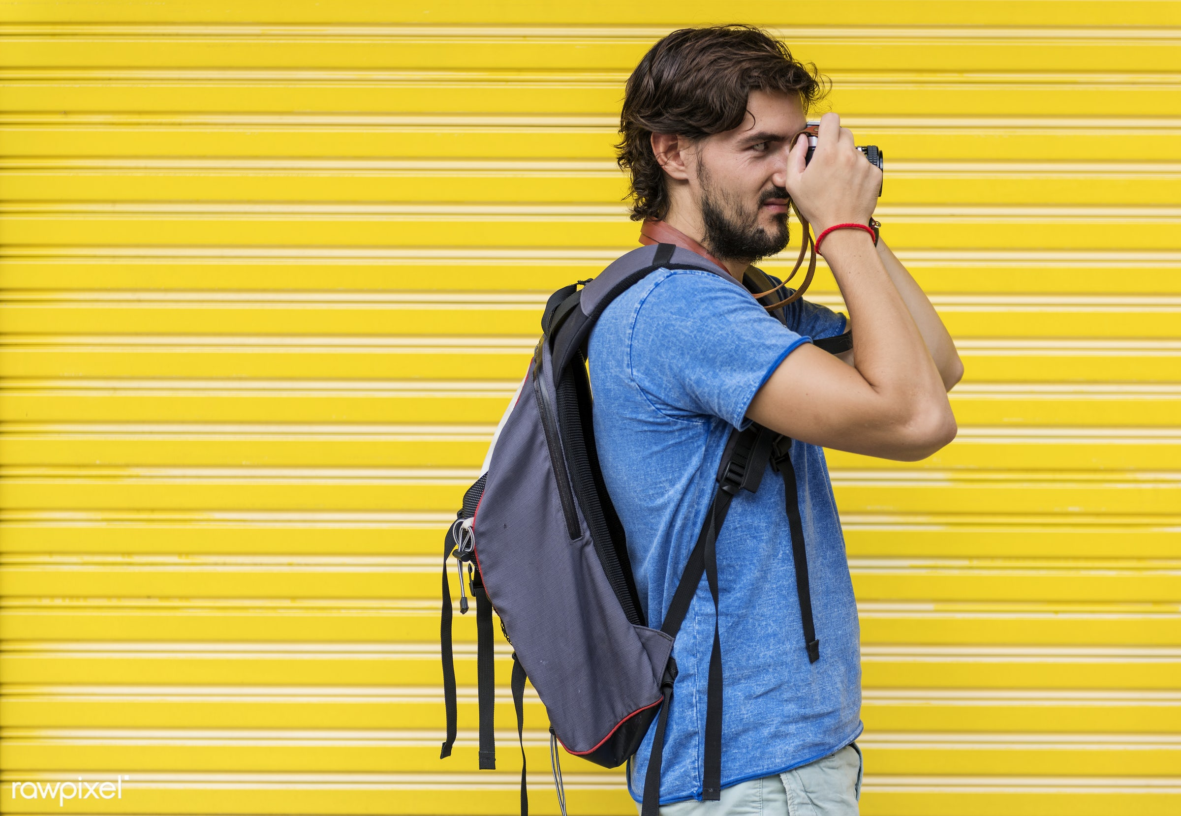 Man with a camera taking a photo - yellow, adult, backpack, backpacker, backpackers, camera, guy, holiday, male, man,...