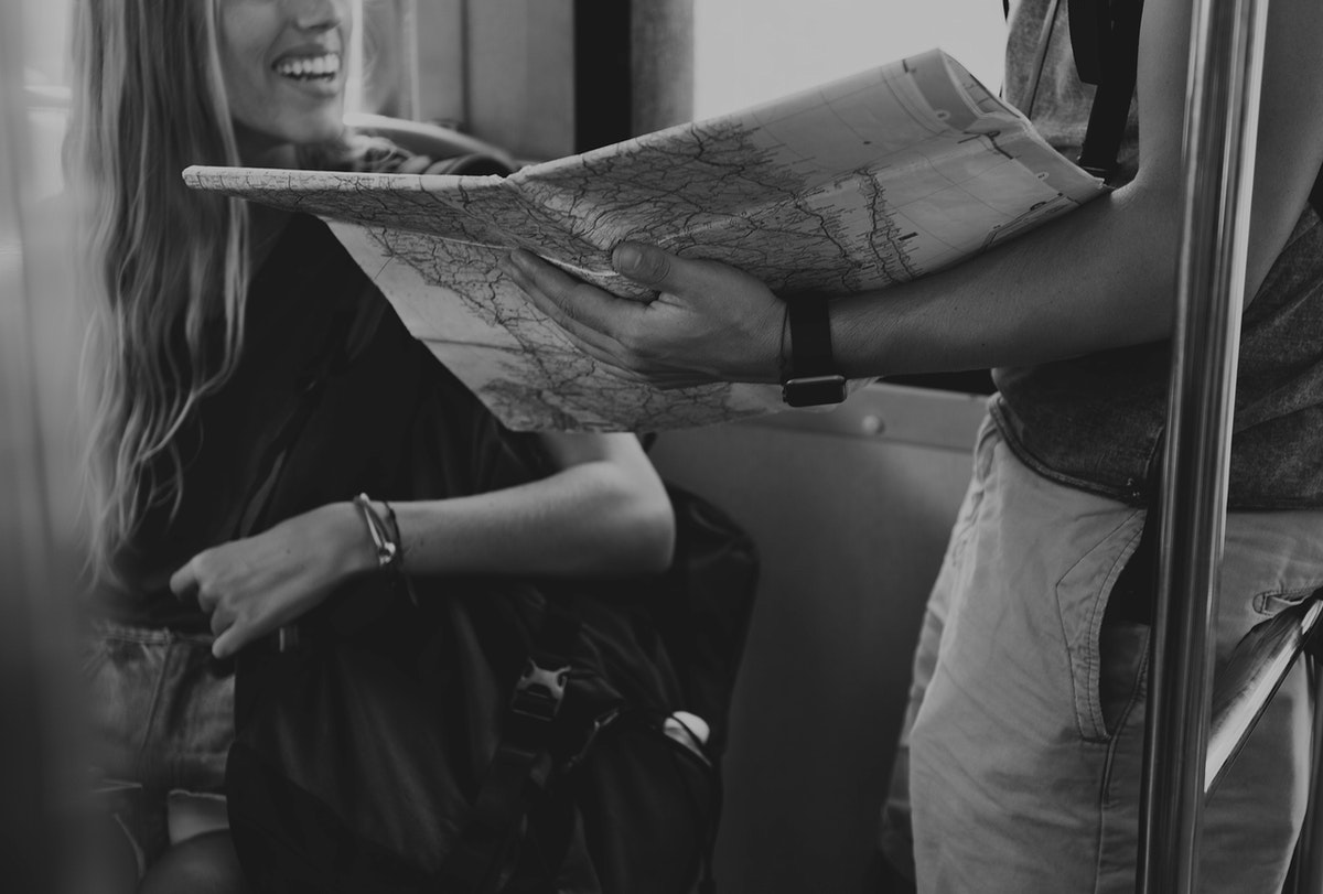 Man holding a map showing her girlfriend their next stop