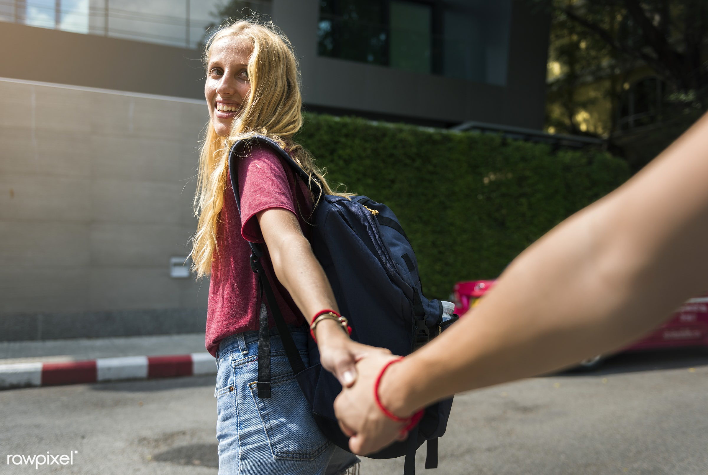 Woman holding hands with her boyfriend - adult, adventure, backpack, backpackers, blonde, boyfriend, city, couple, crossing...