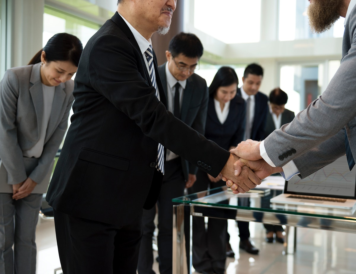 Asian businessman having a handshake with his fellow businessman