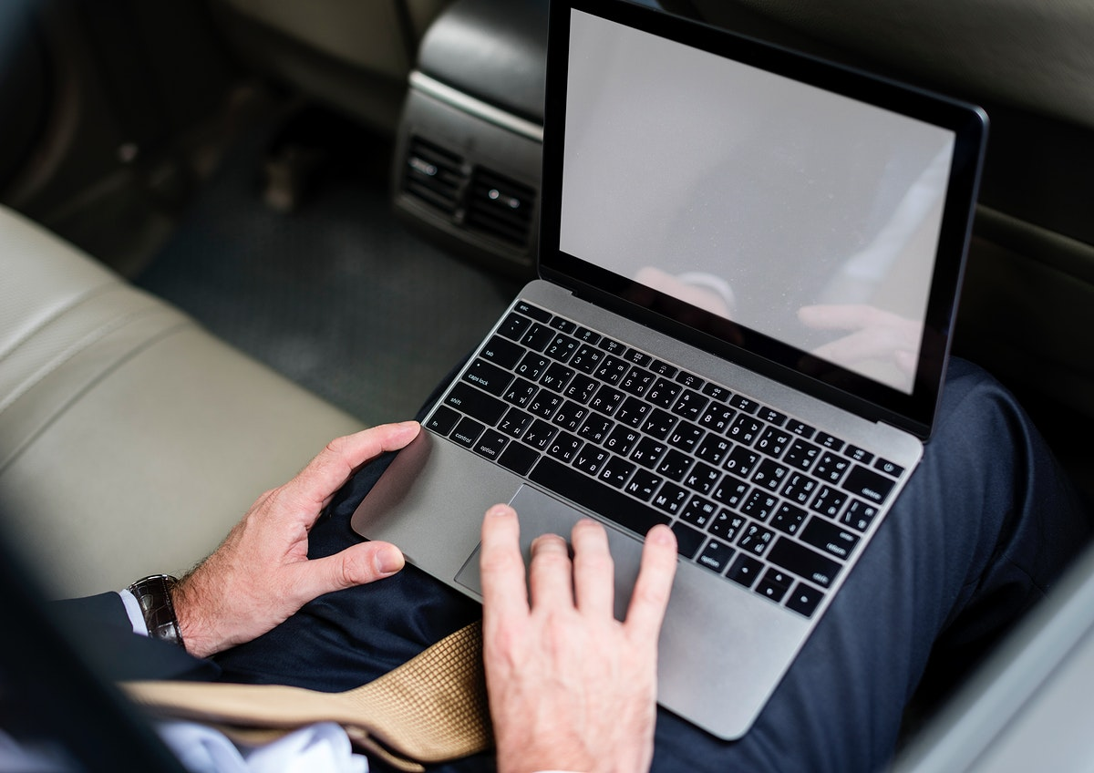 Buusiness People Working Usong Laptop Car Inside