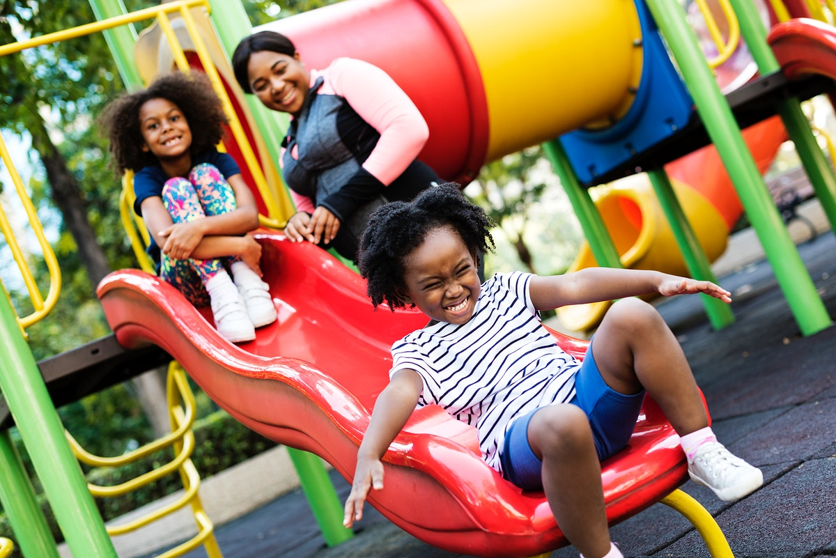 African mother with her two children having fun on a park
