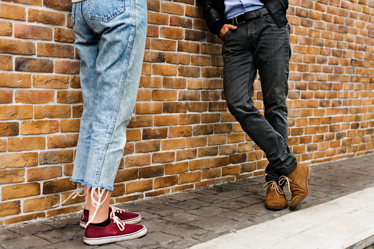Man and woman leaning on a brick wall
