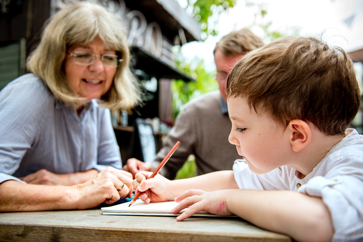 Grandparents helping young boy with coloring  book