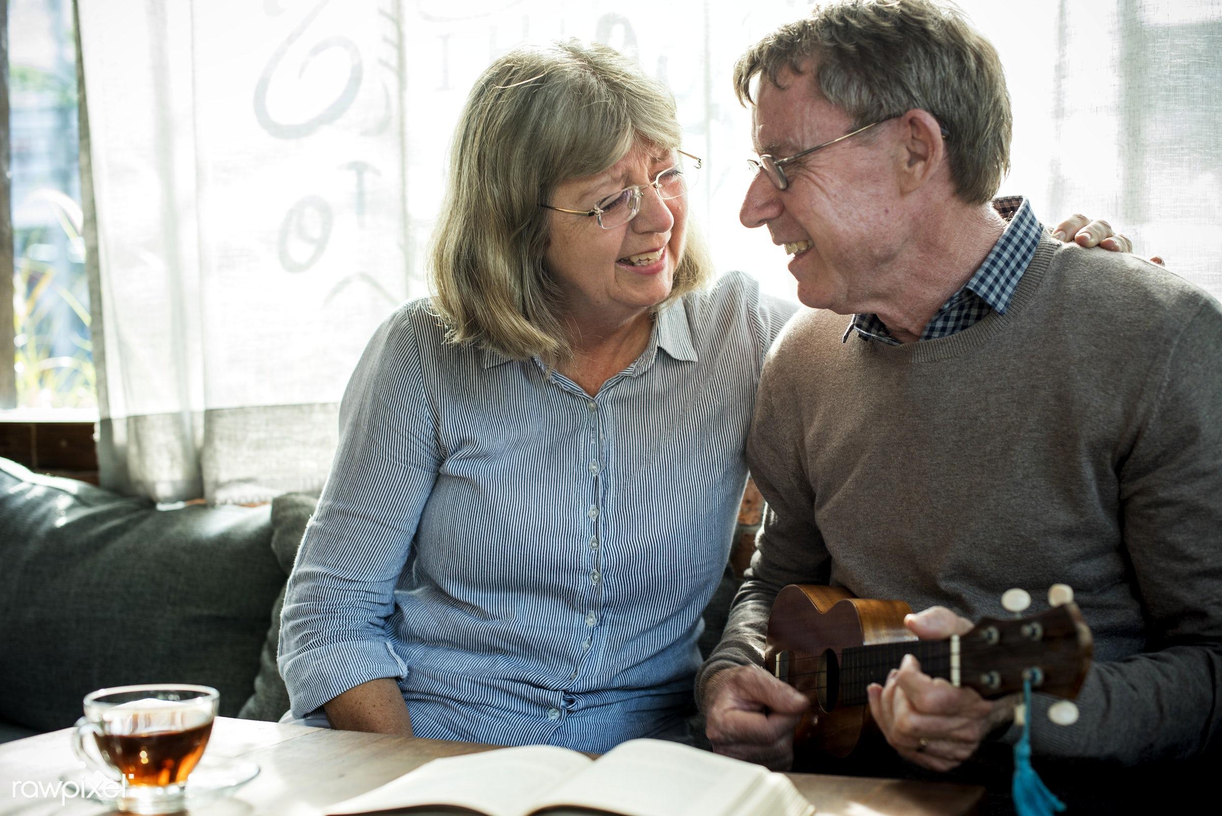 Elderly husband playing ukelele for his wife - marriage, couple, elderly, old, senior, husband, wife, married, ukelele,...