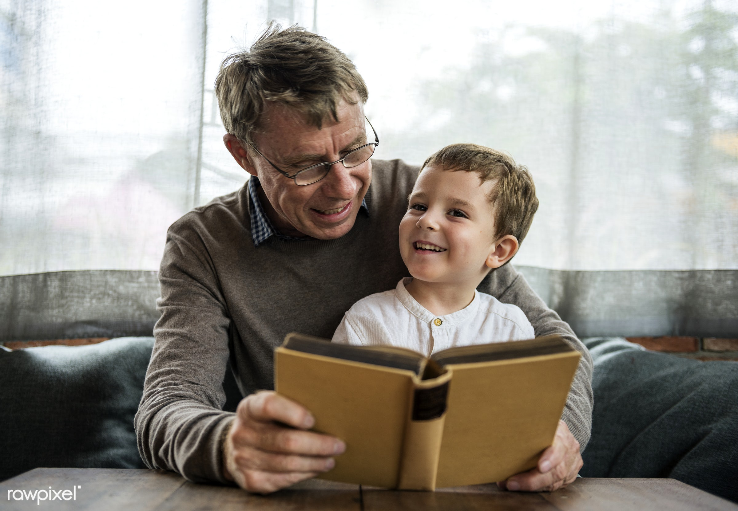 Grandfather and grandson reading a book together - book, boy, child, elderly, grandfather, grandson, kid, people, reading,...
