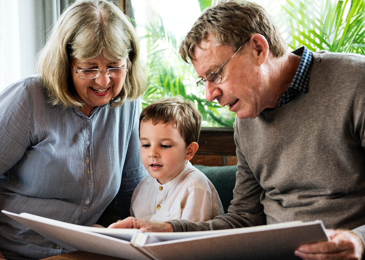 Little boy looking at a picture album with his grandparents