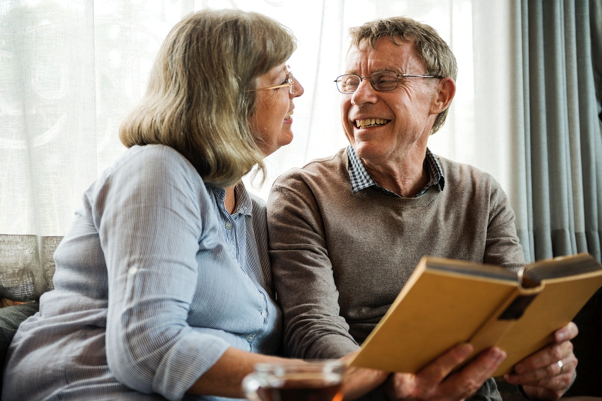 Old caucasian couple reading a book together
