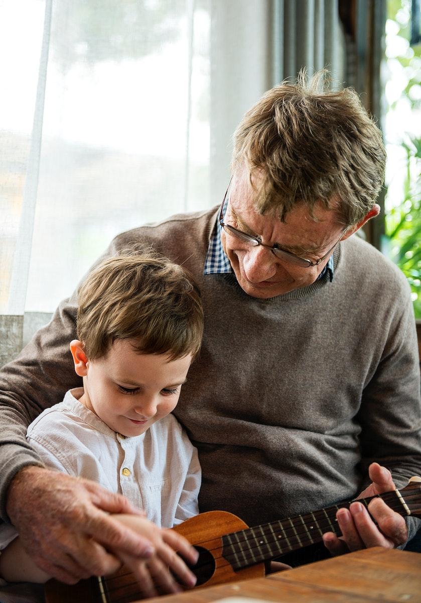 Grandfather teaching grandson how to play ukelele