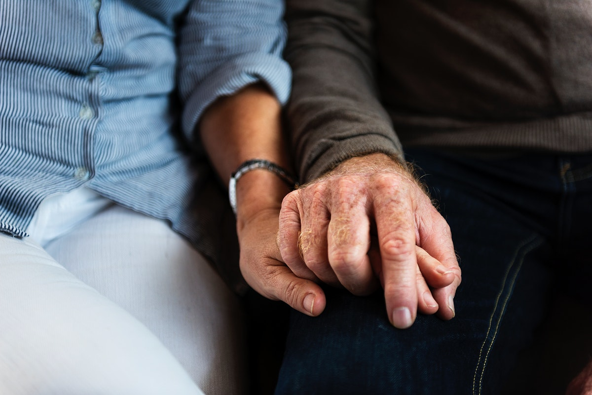 Hands of elderly couple holding each other