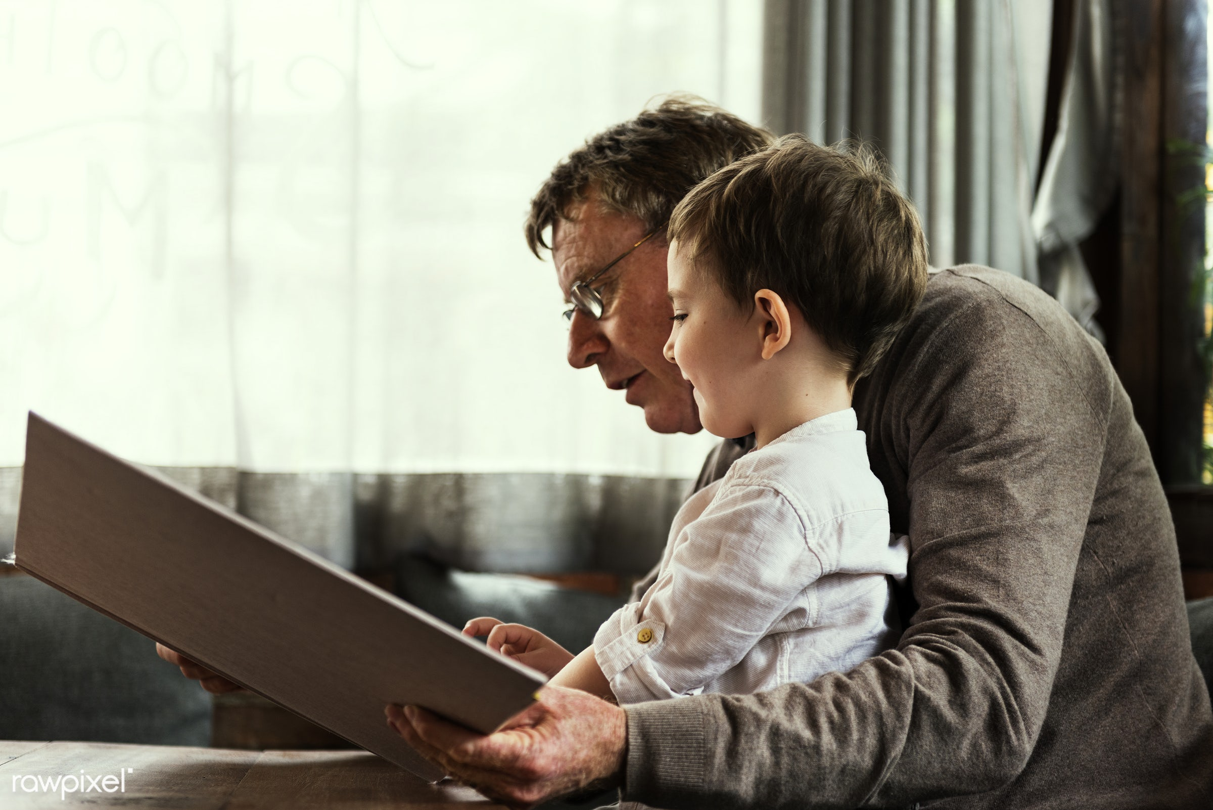 Grandfather and grandson reading a book together - grandson, grandfather, family, boy, young, kid, child, caucasian, reading...