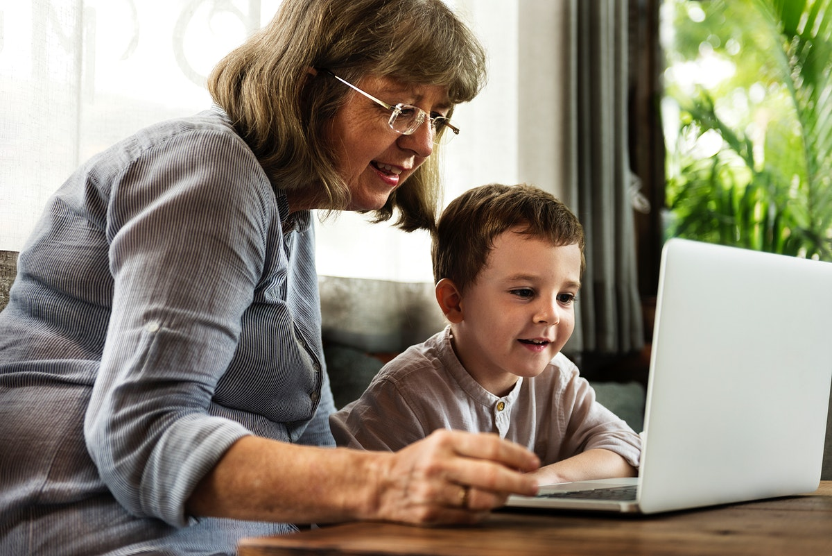 Grandmother and grandson using the laptop together