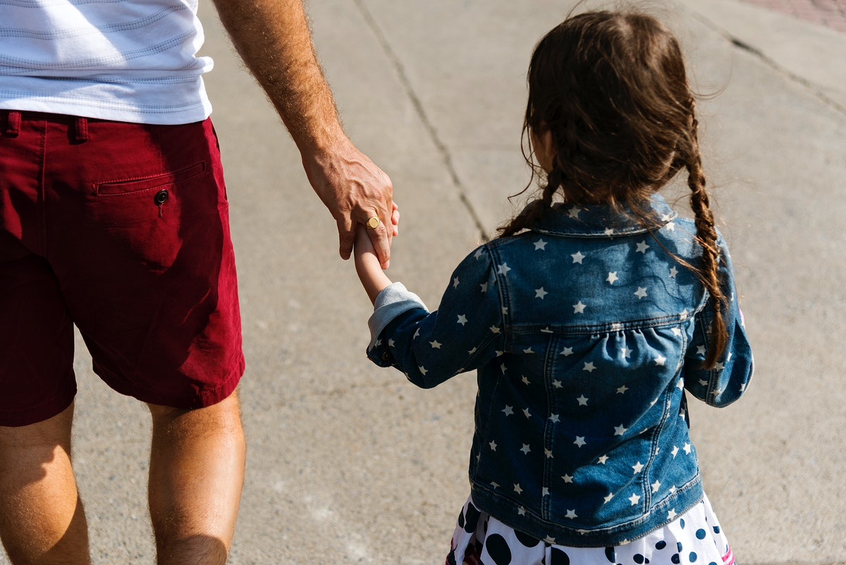 Daughter holding her dad's hand while walking