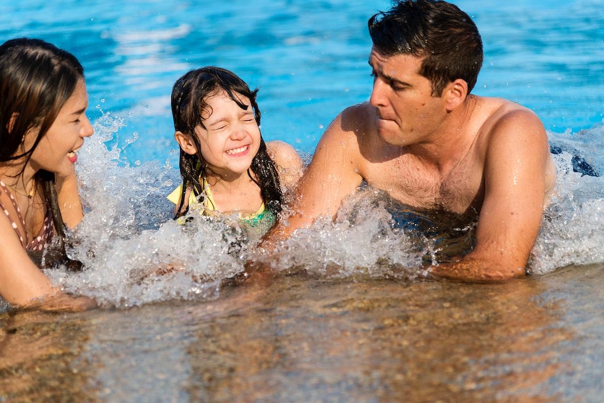 Mixed family enjoying summer pool time