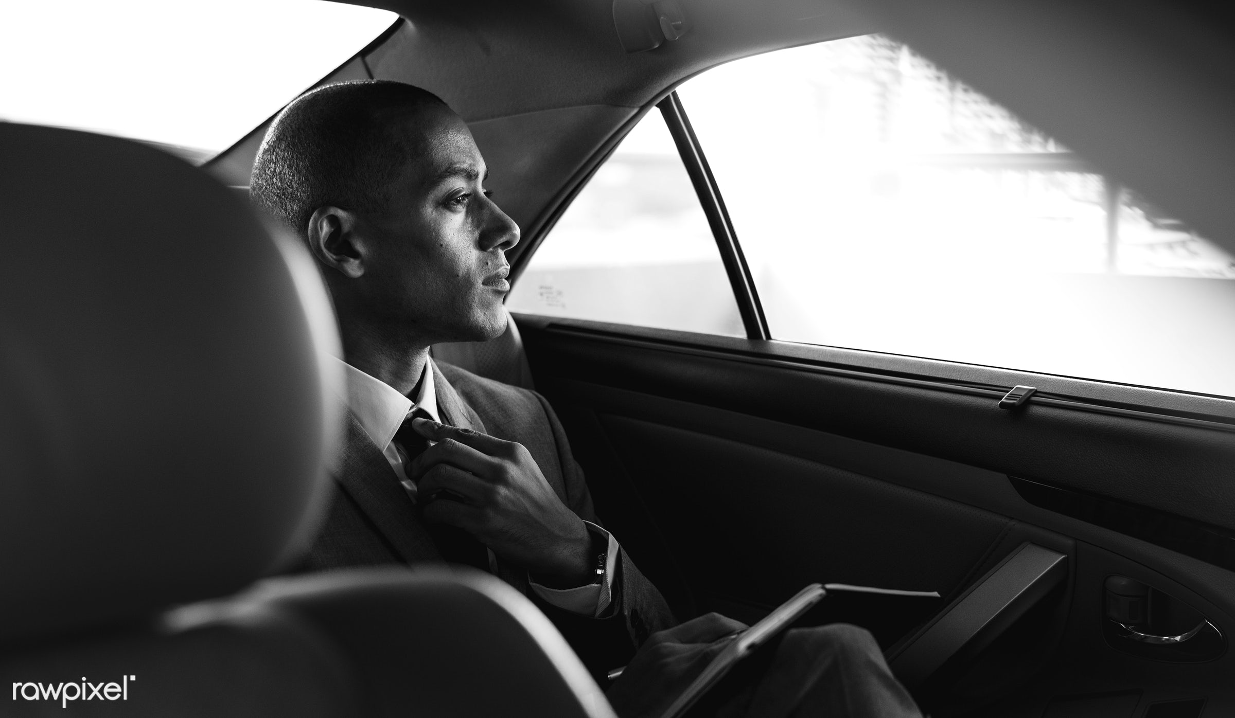 Businessman traveling alone by car - car, corporate, back seat, black and white, business, businessman, businessmen, candid...