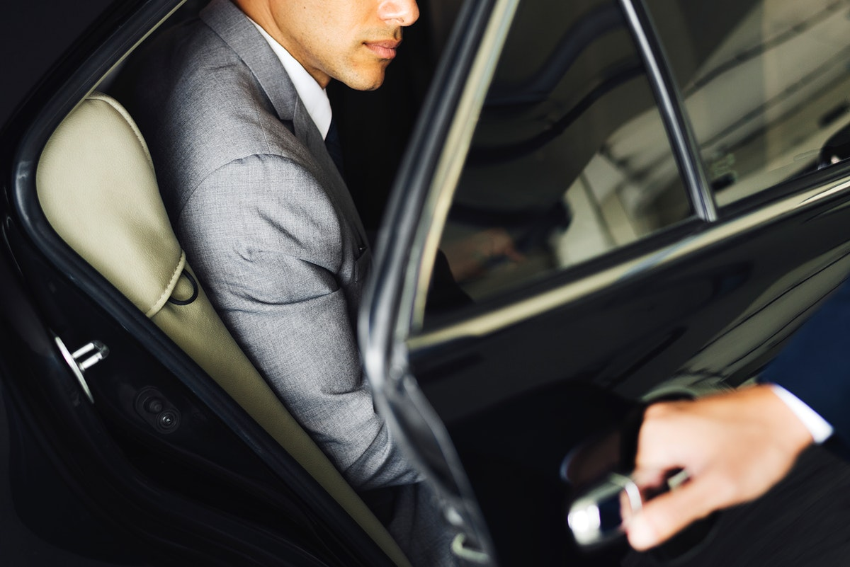 Driver opening door for businessman