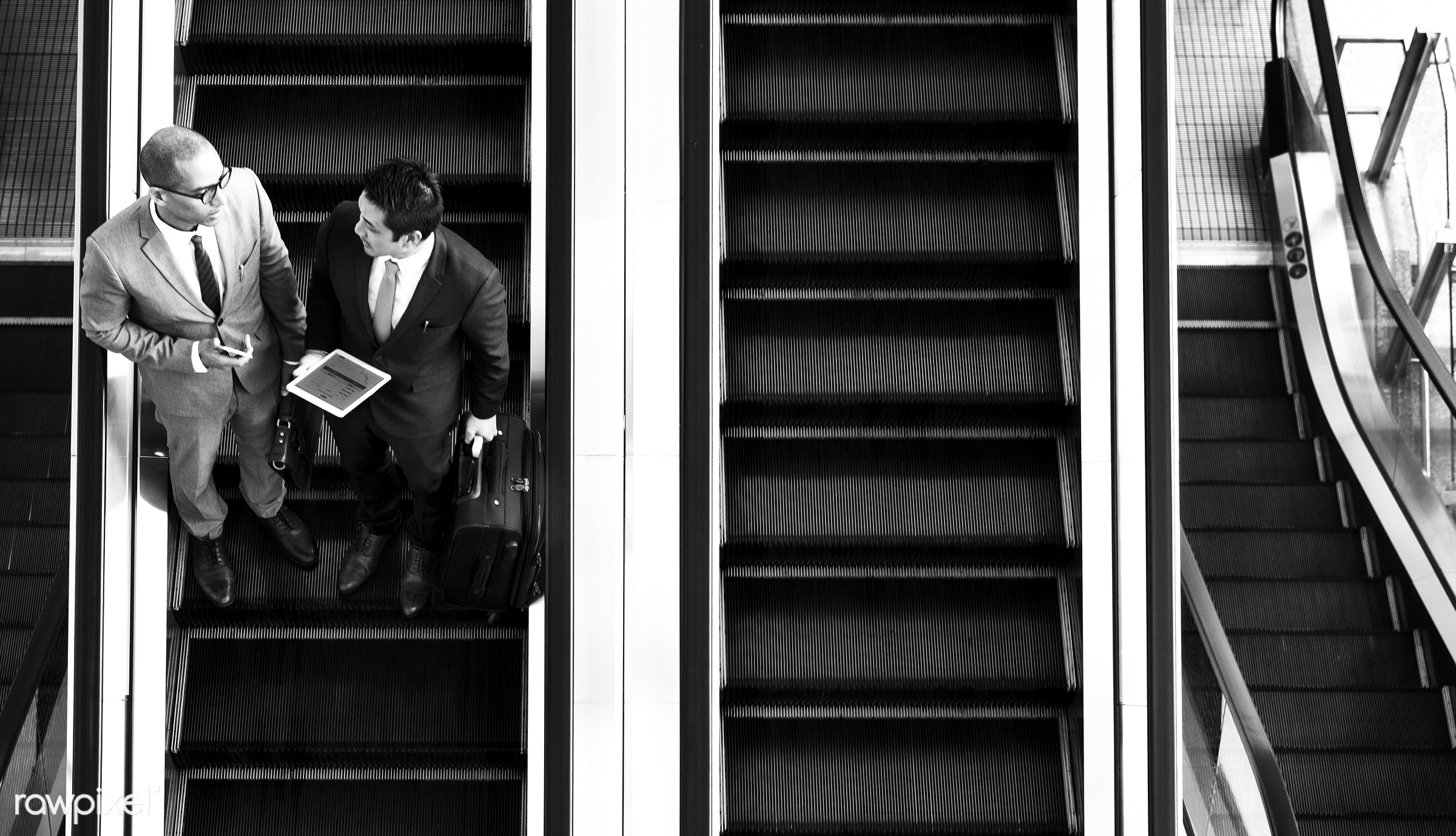 Businessmen on the escalator - asian, business, business men, business people, business travel, businessman, businessmen,...