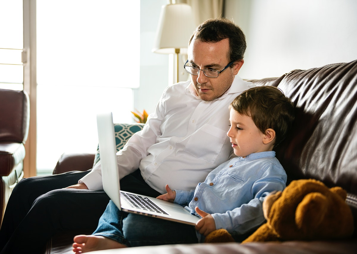 Father teaching son how to use laptop