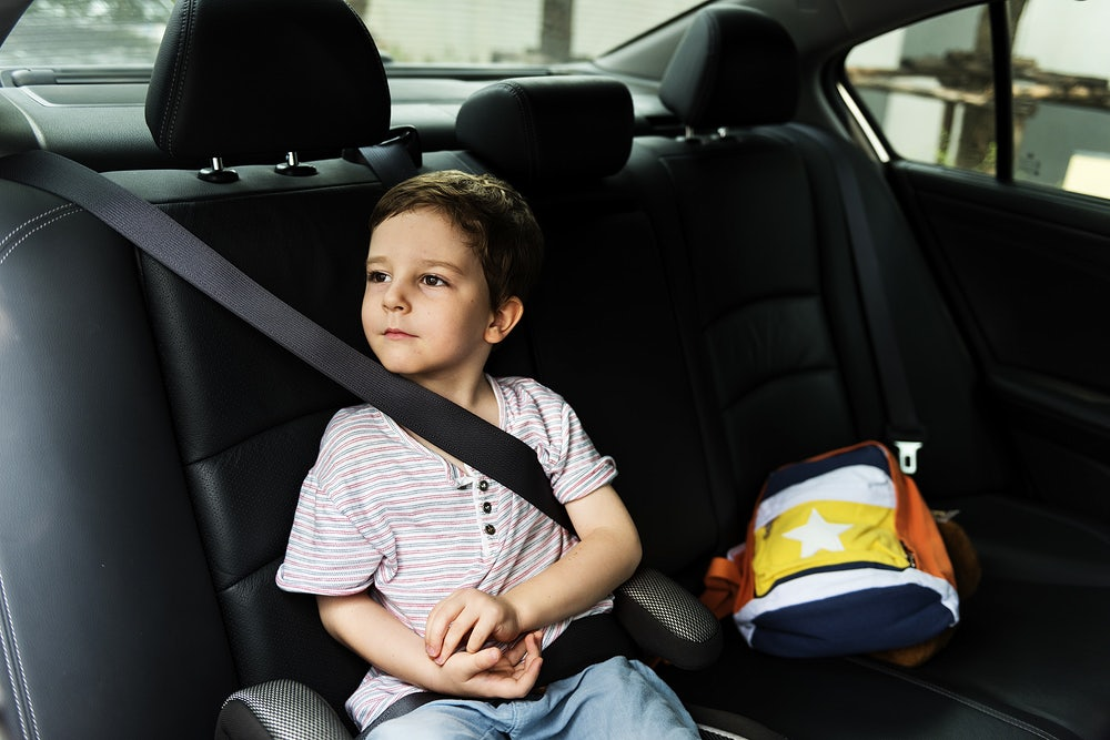 Little boy sitting in the car with seatbelt on for safety