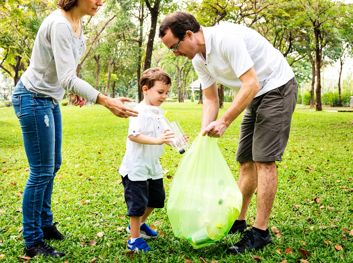 Family picking up trash in the park