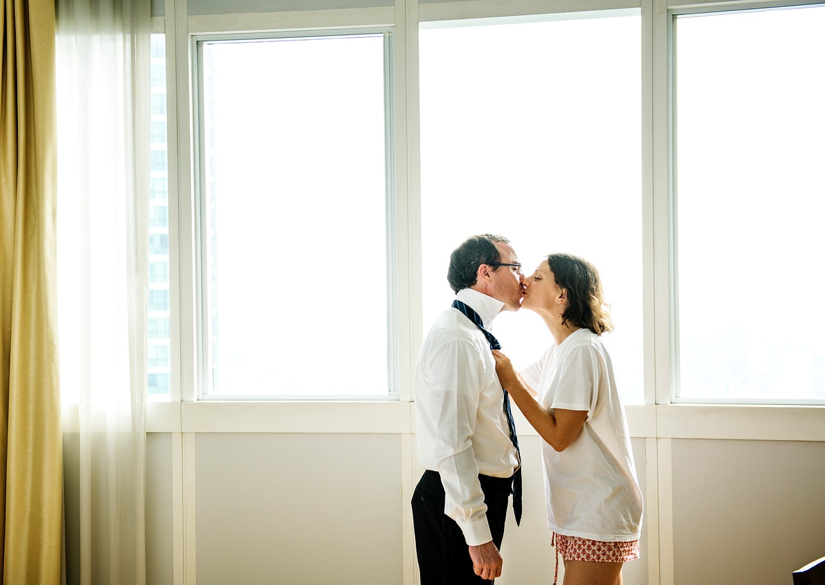 Woman kissing husband goodbye in the morning