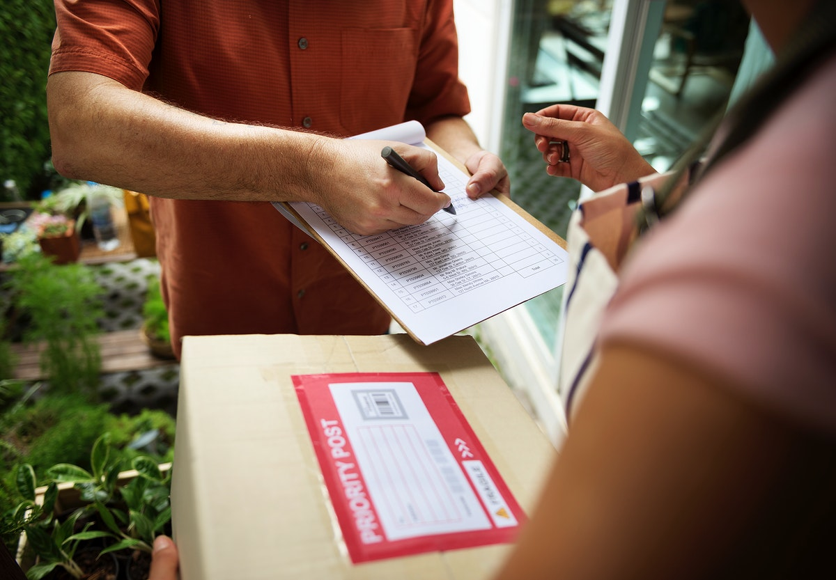 Closeup of hand signing on delivery paper