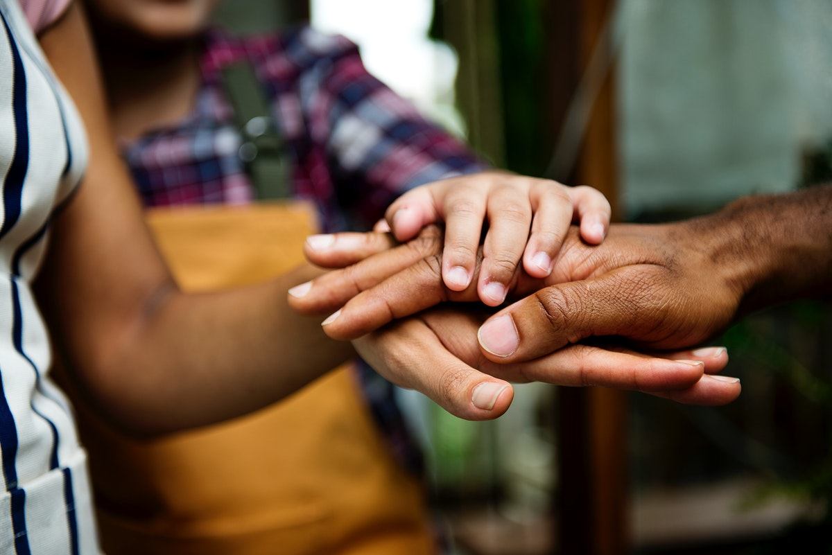 Closeup of diverse hands joined together as teamwork