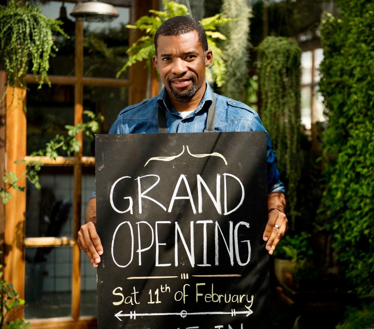 Man with grand opening blackboard
