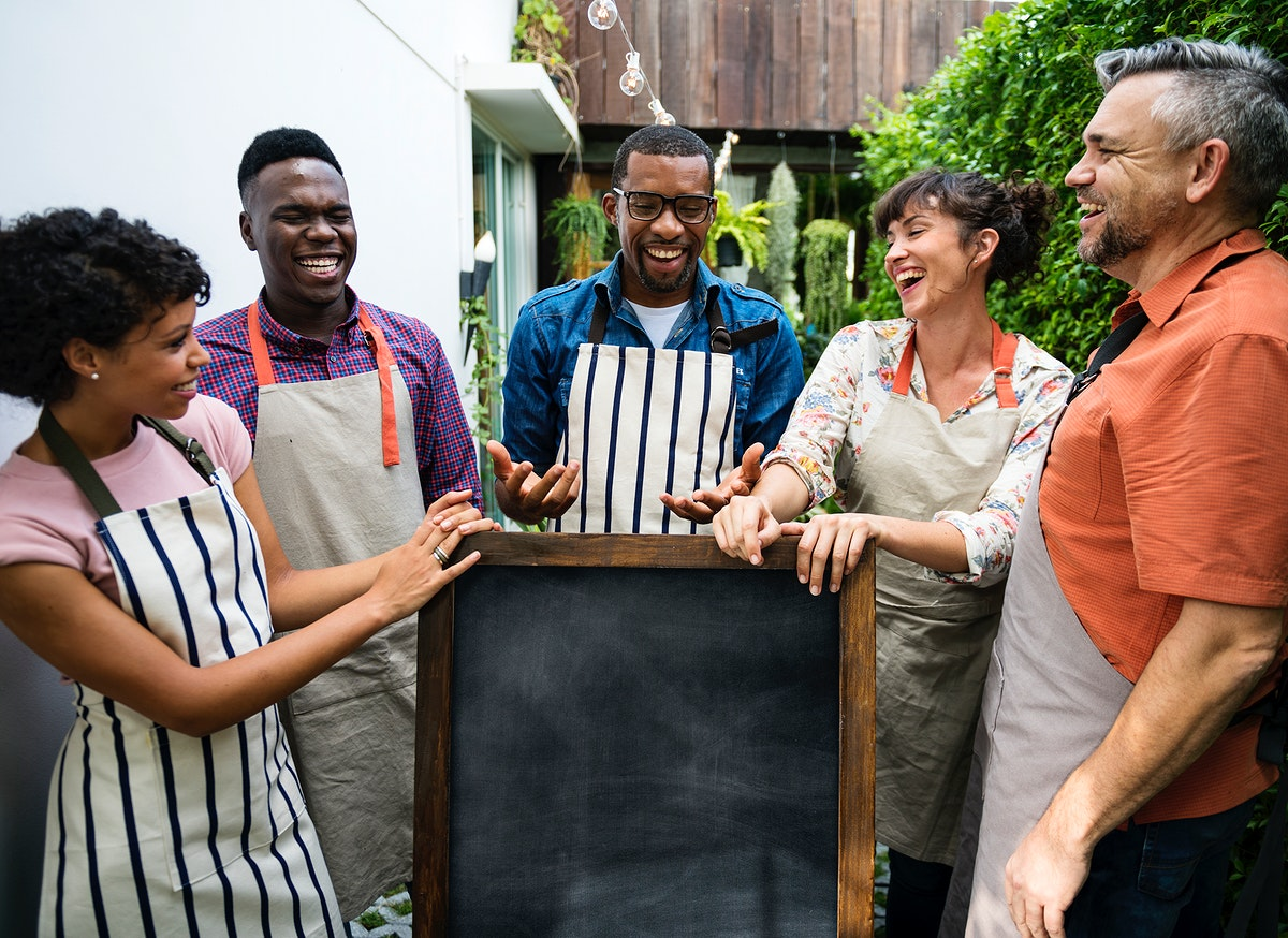Group of diverse people with blank chalkboard