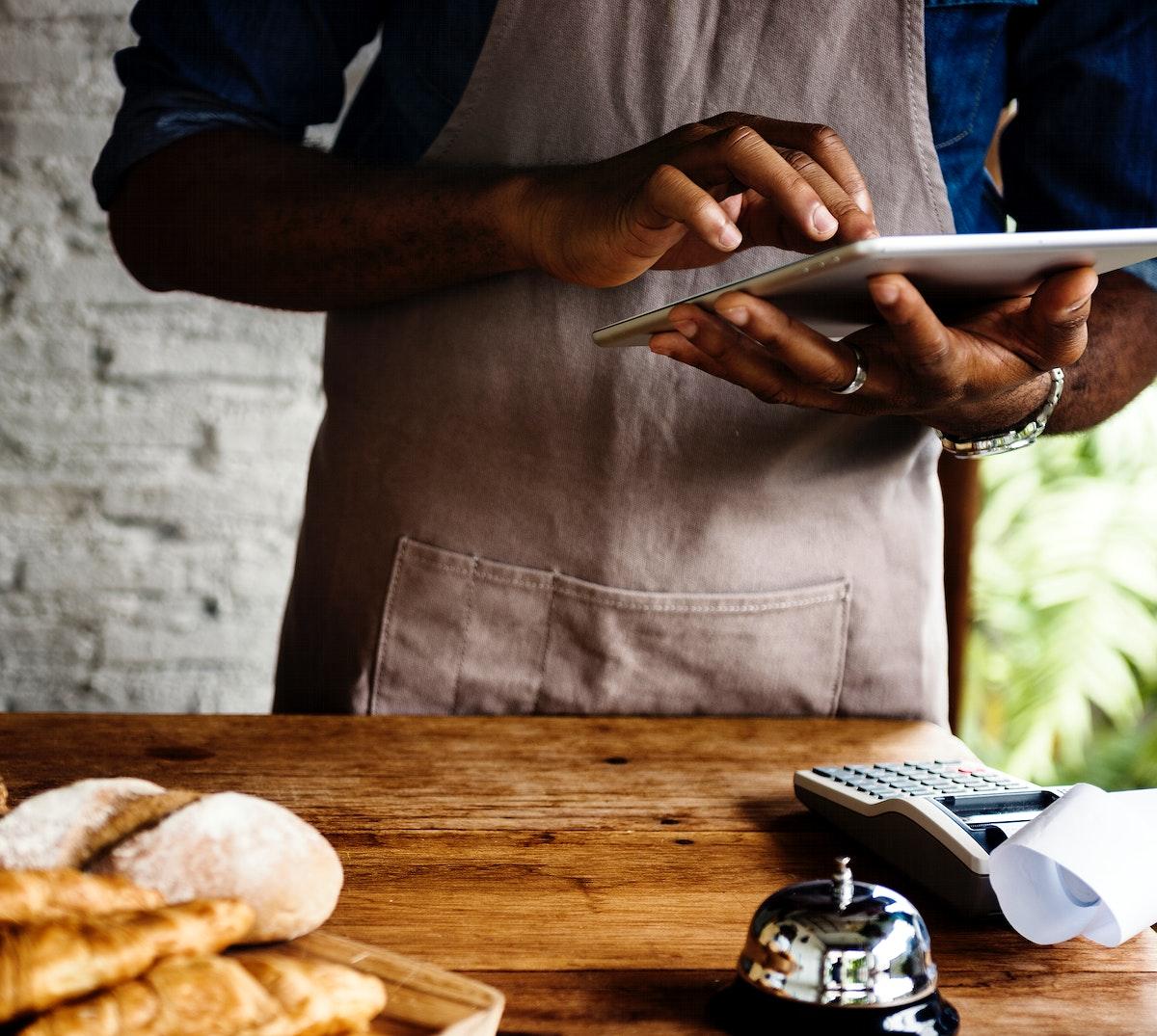 Man using digital tablet in baker's shop