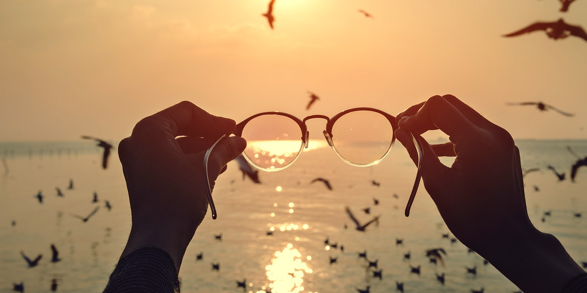 Hands holding out eyeglasses to sea and sunset