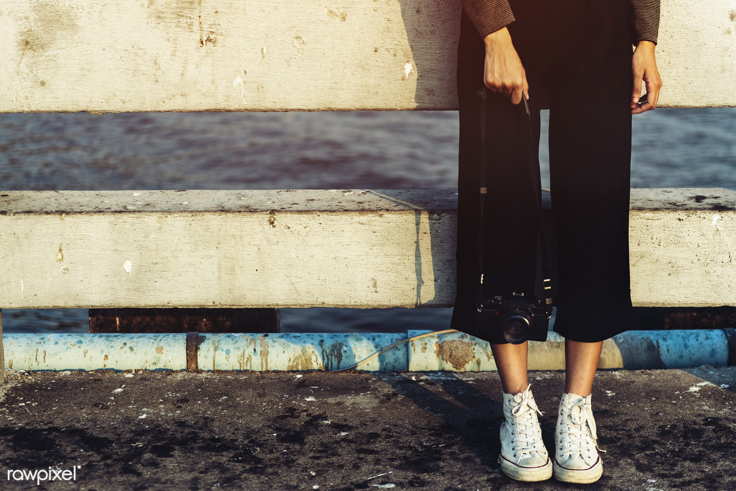 Woman's legs standing holding a camera - legs, feet, standing, shoes, casual, outdoors, alone, solitude, camera, leisure,...