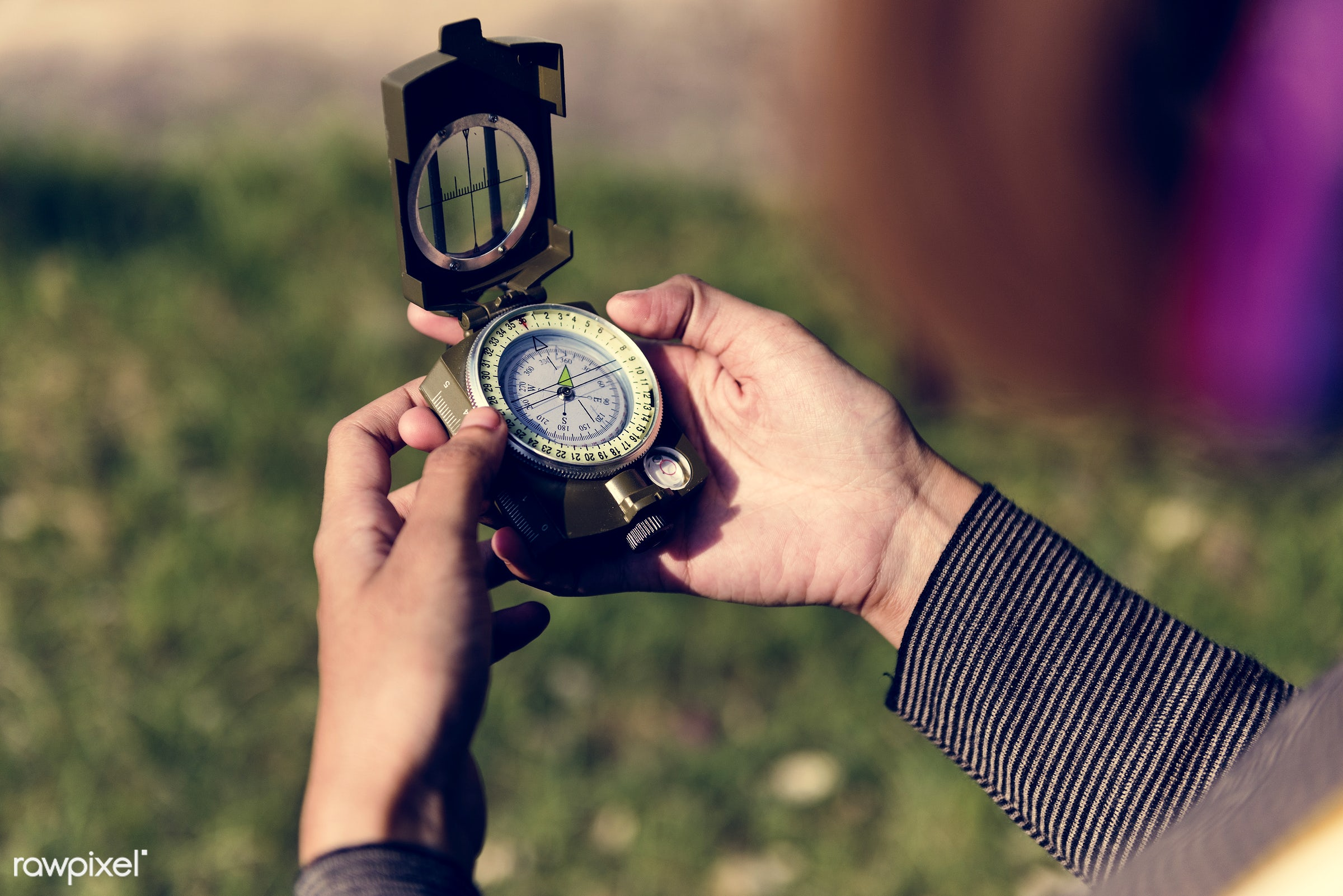 hand, holding, compass, direction, navigation, equipment, tool, aerial, grass, leaves, outdoors