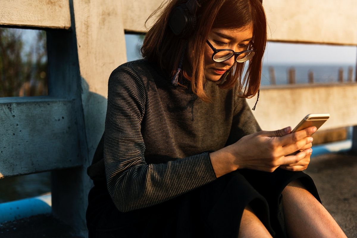Girl with glasses using her mobile phone
