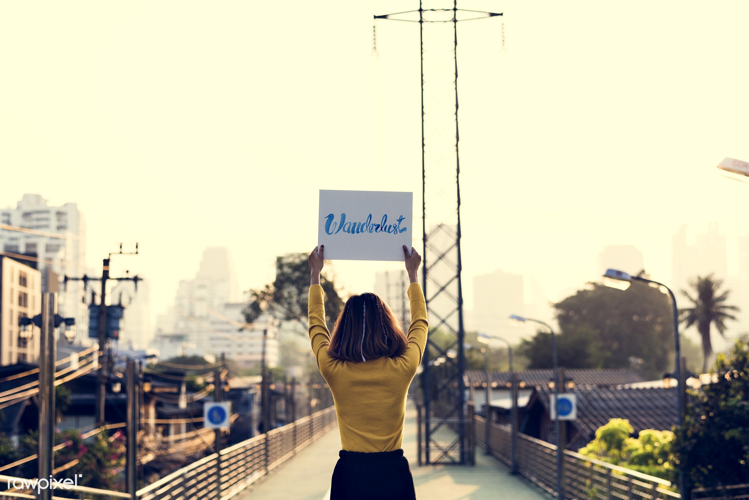 holding, woman, girl, wanderlust, trip, travel, text, signage, banner, standing, person, placard, rear view, city
