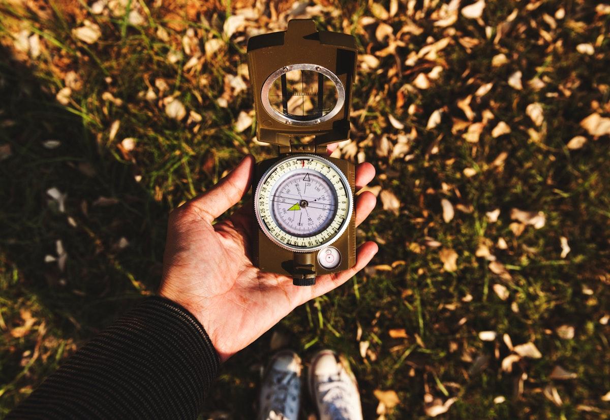 Closeup of hand holding a compass