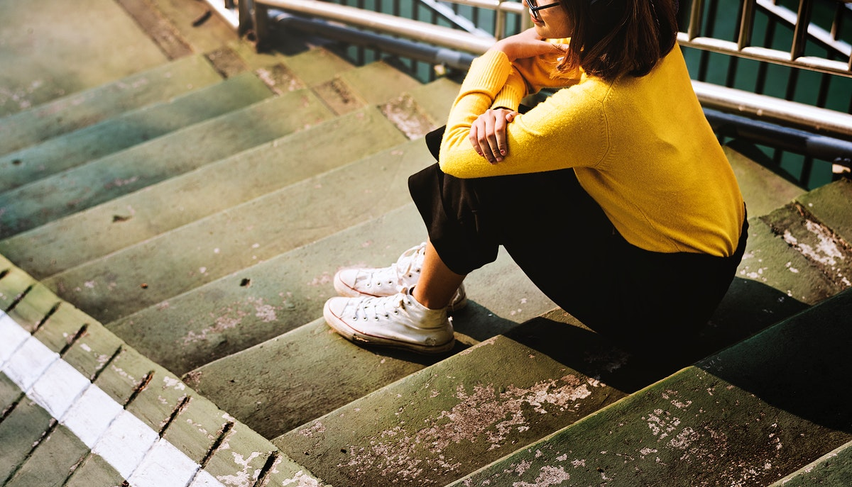 Girl sitting on the steps of a staircase