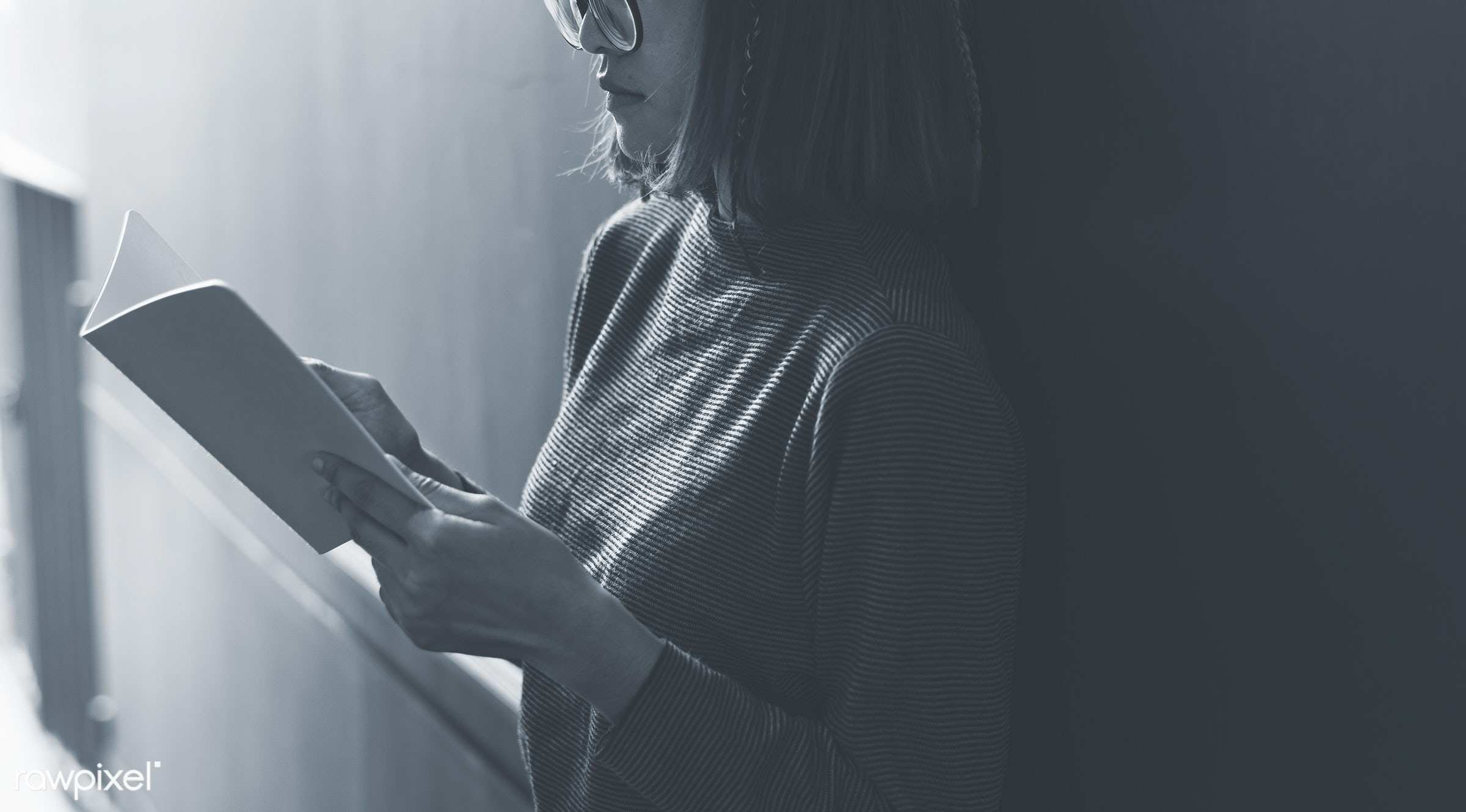 Girl with glasses reading a book - girl, woman, asian, reading, book, hobby, wall, alone, solitude, bookworm, alley, person
