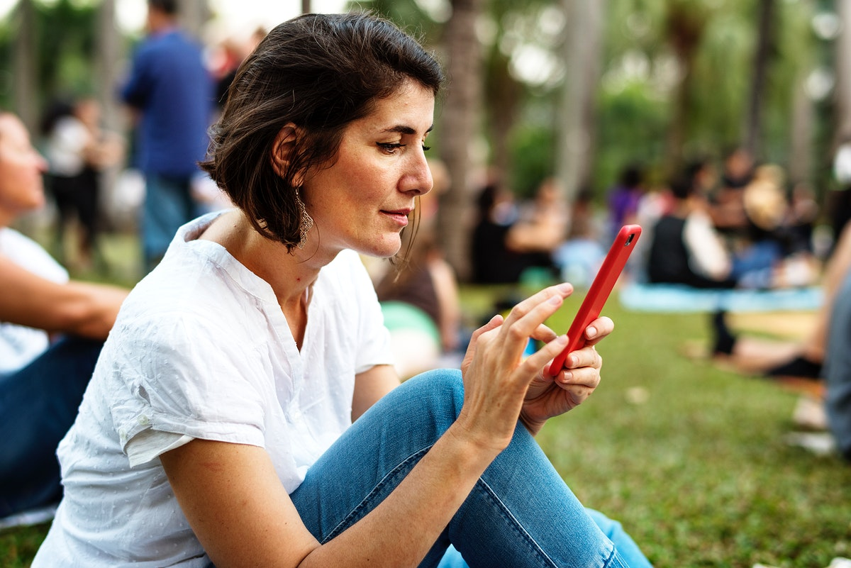 An Adult Woman Sitting in The Park Using Mobile Phone