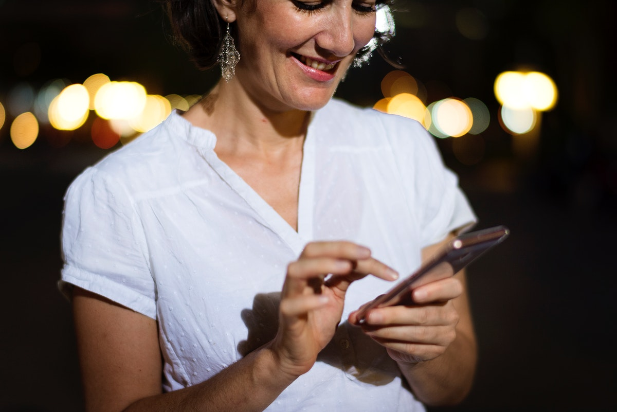 Woman using smart phone walking on street night time