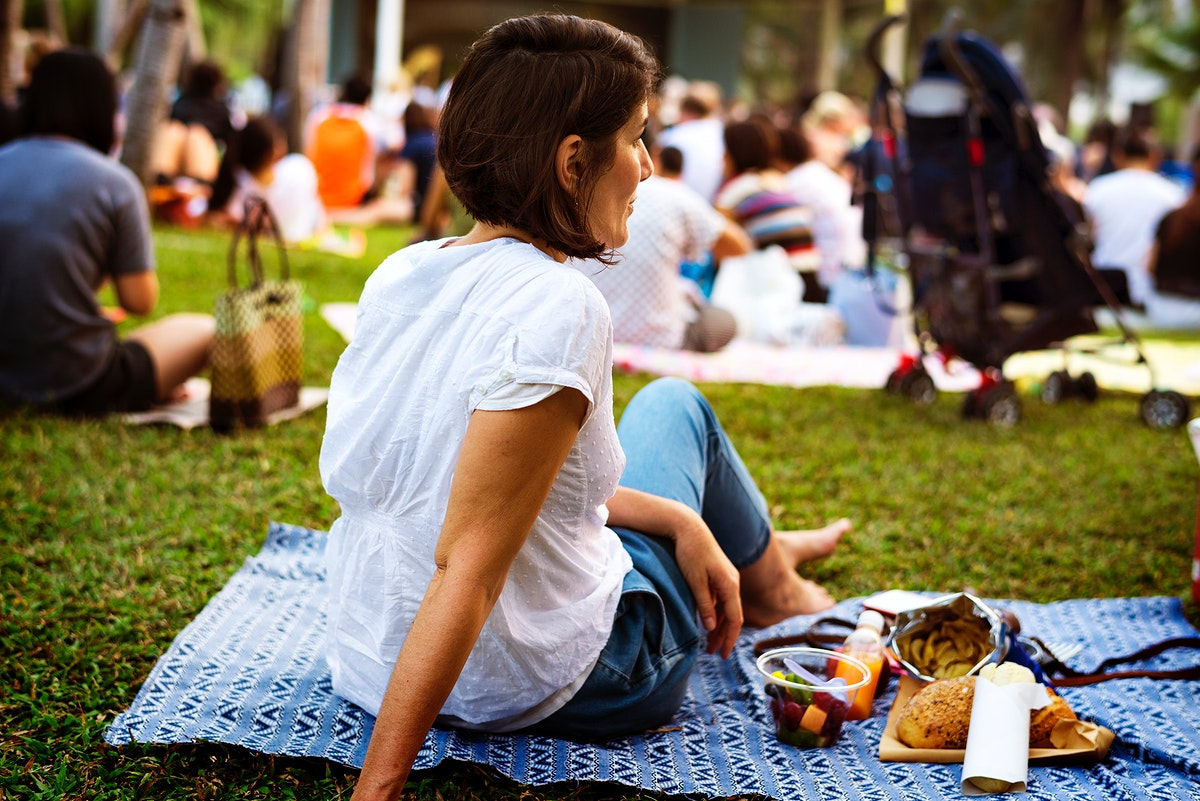 An Adult Woman Sitting and Picnicking in The Park