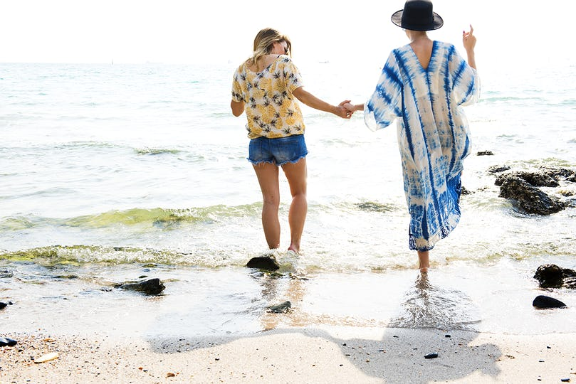 Girlfriends holding hands and walking on the beach