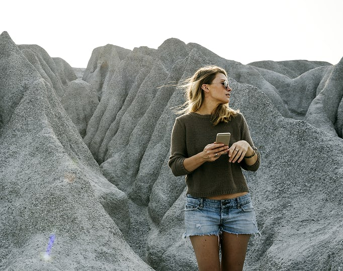 Woman hiking to the top of mountain in nature