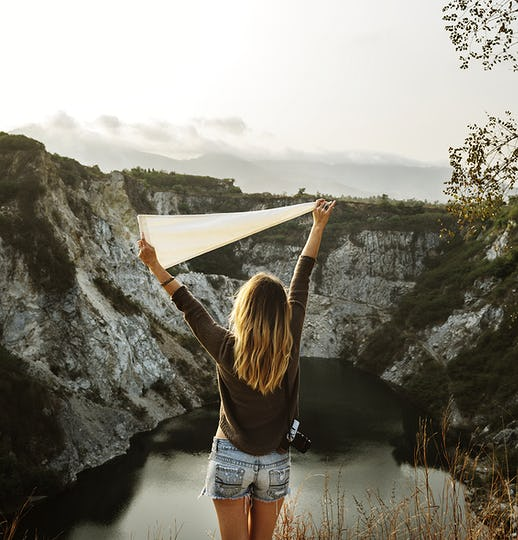 Woman arms raised and holding flag on mountain
