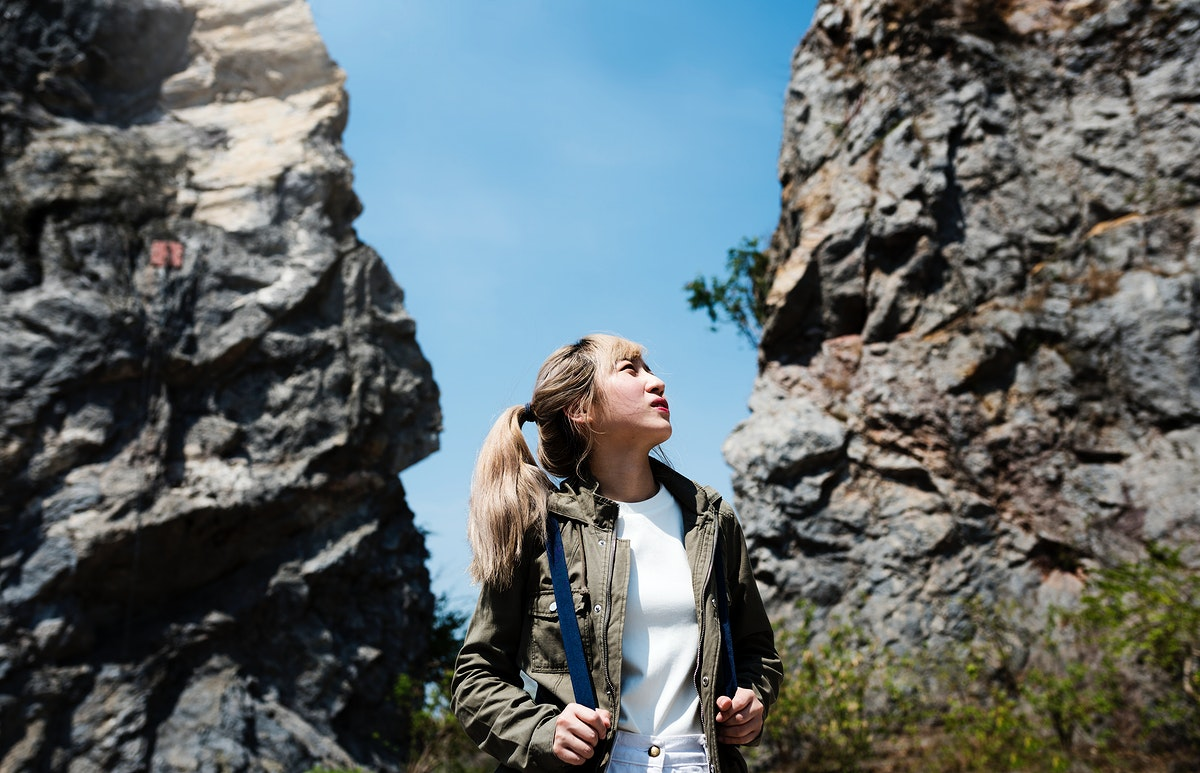 Woman standing in the middle of two rock structure looking lost