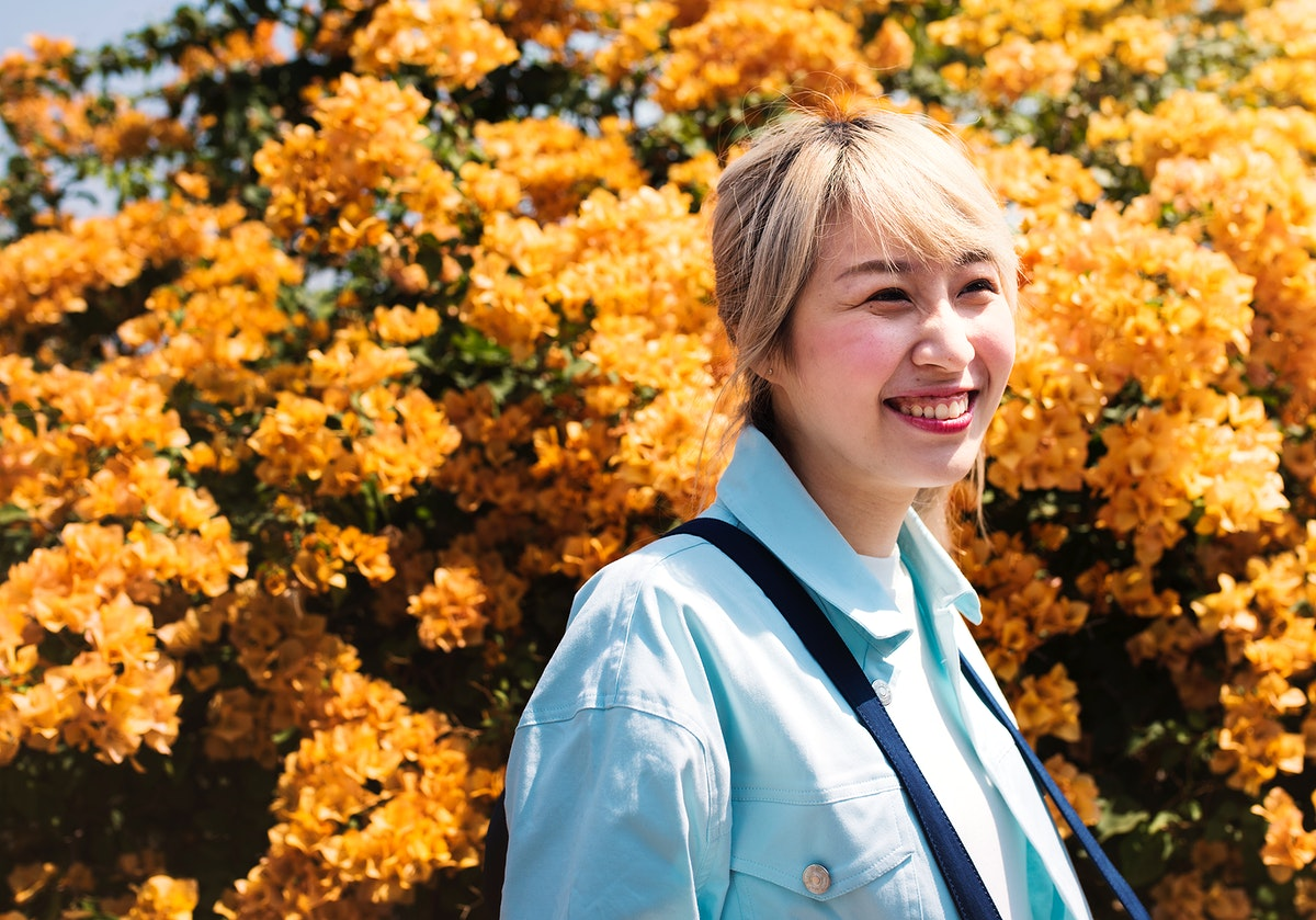 Asian woman with orange flowers in the background